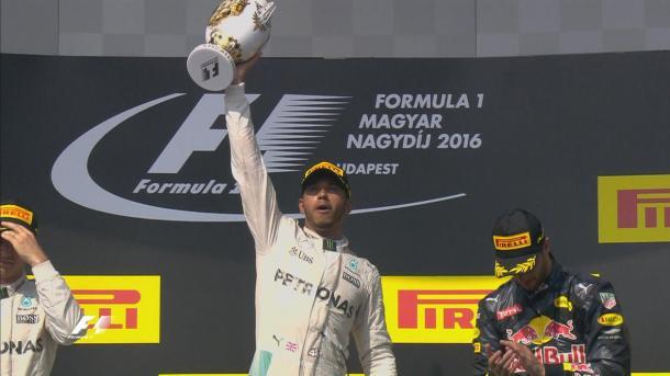 Hamilton comemorando com o seu troféu no pódio (Foto: Divulgação/F1)
