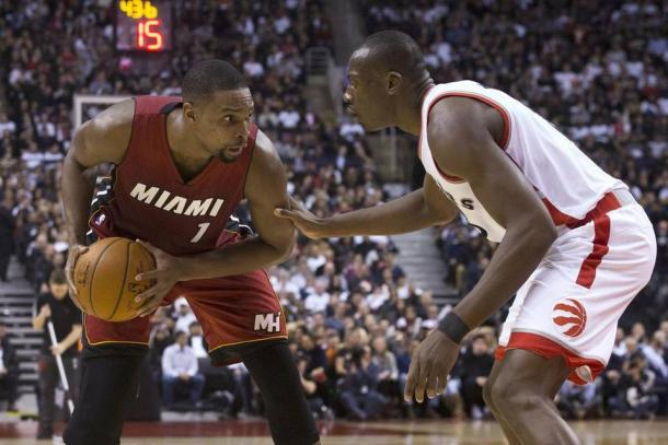Miami Heat's Chris Bosh (1) faces off with Toronto Raptors' Bismack Biyombo (8) during the second half Friday, Jan. 22, 2016, in Toronto. Chris Young AP