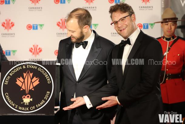 Seth Rogen humorously shows off his star while co-star Evan Goldberg takes a minute to admire their names literally etched in stone.