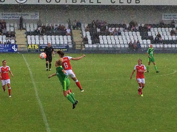 Losada and Furness both go for the ball as the rain lashes down