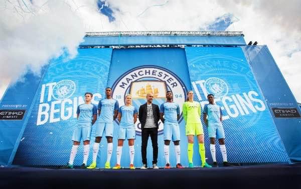 Pep Guardiola posa junto a futbolistas del Manchester City con la nueva equipación | Foto: MCFC
