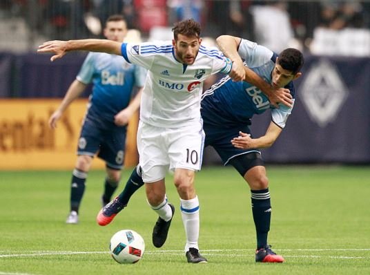 Ignacio Piatti (center) of the Montreal Impact holds off Matias Laba (right) of the Vancouver Whitecaps and he dribbles the ball upfield during their MLS game March 6, 2016 at BC Place in Vancouver, British Columbia, Canada. Montreal won 3-2 / Jeff Vinnick - Getty Images