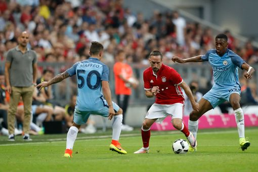 Franck Ribéry with the ball as his former boss watches on. | Photo: Manchester Evening News
