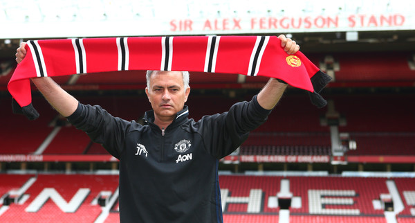 Mourinho holds aloft a Manchester United scarf | Photo via Getty Images