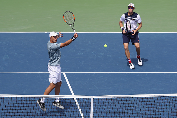 Henri Kontinen hits a volley with partner John Peers looking on (Photo: Elsa/Getty Images)