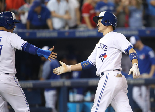 Darwin Barney (R) is congratulated by Ryan Goins after hitting a two-run homer in the bottom of the sixth inning to get the Blue Jays to draw first blood. | Photo: Photo: Tom Szczerbowski/Getty Images