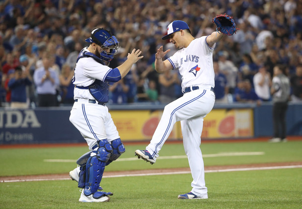 Roberto Osuna and Russell Martin celebrate after Osuna clinched his career-high 37th save of the season. | Photo: Tom Szczerbowski/Getty Images