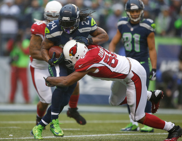 Karlos Dansby (56) of the Cardinals tackling Marshawn Lynch (24) of the Seahawks in a game in 2013 at CenturyLink Field in 2013 |Source: Otto Greule Jr/Getty Images North America|