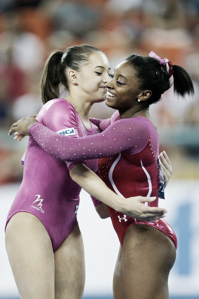 Larisa Iordache and Simone Biles appear to be embracing after a competition. Photo Credit: Lintao Zhang of Getty Images