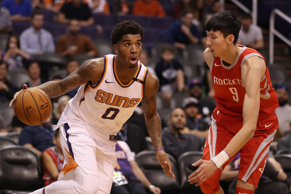 Marquese Chriss #0 of the Phoenix Suns moves the ball past Zhou Qi #9 of the Houston Rockets on November 16, 2017 in Phoenix, Arizona. The Rockets defeated the Suns 142-116. |Christian Petersen/Getty Images North America|