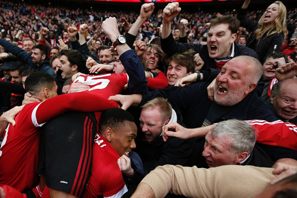 Anthony Martial is mobbed after scoring the winning goal in the 93rd minute | Photo: Adrian Dennis/AFP