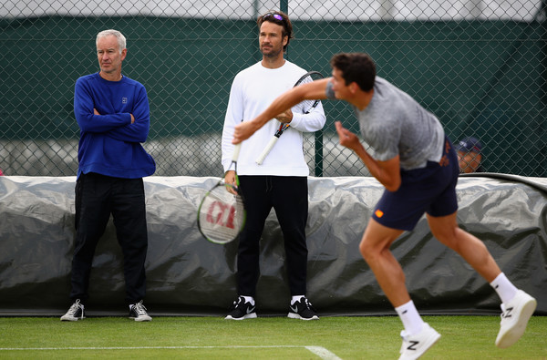 Supercoaches John McEnroe (left) and Carlos Moya (centre) look on during a practice with Milos Raonic (right, serving) at WImbledon in July. Photo: Clive Brunskill/Getty Images)
