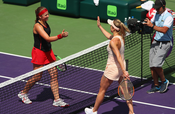 Ostapenko and Svitolina meet at the net following their tight encounter (Getty Images North America/Clive Brunskill)