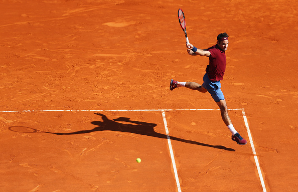 Federer leaps as he sends a backhand down the line for a winner against Tsonga. Credit: Michael Steele/Getty Images