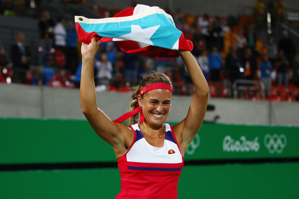 An ecstatic Monica Puig does a victory lap with the Puerto Rican flag after becoming the nation's first Olympic gold medallist. | Photo: Clive Brunskill/Getty Images