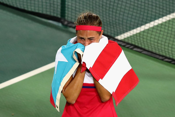 Monica Puig celebrates with the Puerto Rican flag around her shoulders after defeating Angelique Kerber in the women's gold medal match on Day 8 of the Rio 2016 Olympic Games. | Photo: Clive Brunskill/Getty Images South America