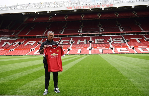 Mourinho poses with a Manchester United shirt at his unveiling | Photo: Oli Scarff/AFP