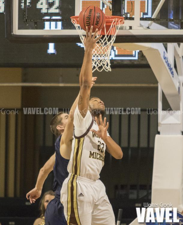 Reggie Jones (23) gets the one handed basket from under the hoop. Photo: Walter Cronk