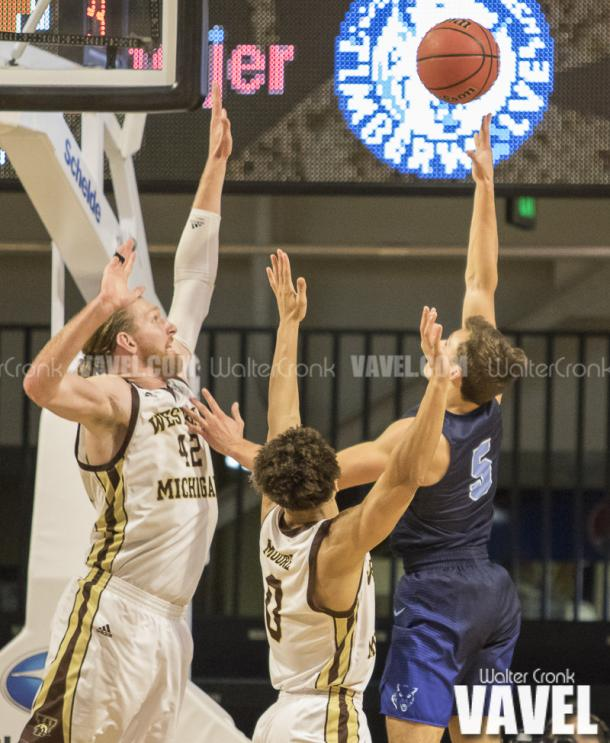 Nate Georgeton (5) tries to take the shot over WMU defenders Drake LaMont (42) and Bryce Moore (0). Photo: Walter Cronk