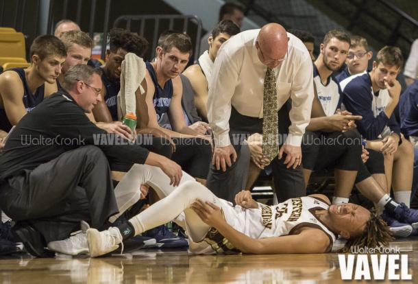 Coach Steve Hawkins looks over Brandon Johnson(35) after he go's down with what they hope isnt a serious injury late in the game. Photo: Walter Cronk