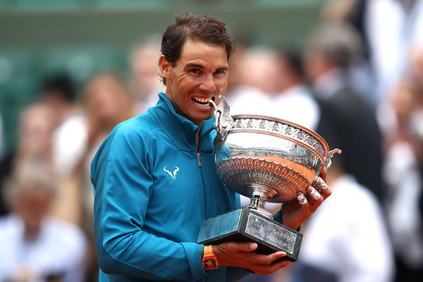 Nadal bites into his 11th Roland Garros trophy earlier this month. Photo: Cameron Spencer/Getty Images