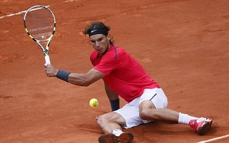 Nadal returns a shot despite falling during the 2012 French Open final. Photo: AFP/Getty Images