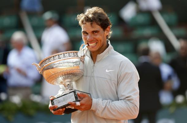 Rafael Nadal bites his most recent French Open singles trophy in 2014. Photo: Reuters