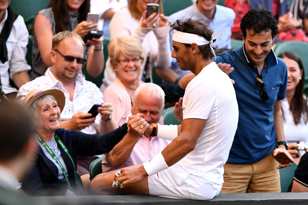Nadal shakes hand with a fan after crashing into the stands after a long rally in the fifth set. Photo: Clive Mason/Getty Images