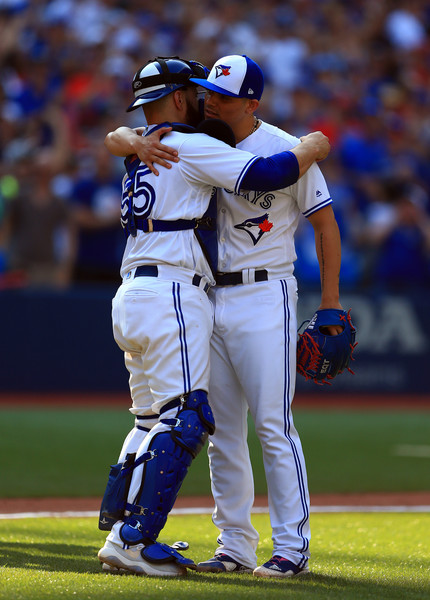 Closer Roberto Osuna celebrates with catcher Russell Martin after closing out the Blue Jays' last home game of the season. | Photo: Vaughn Ridley/Getty Images