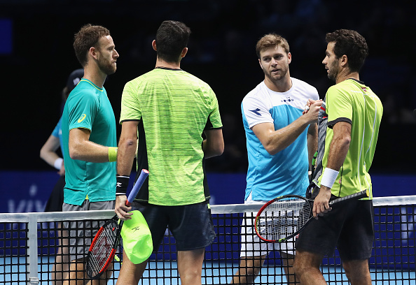 Jean-Julien Rojer and Horia Tecau shake hands with the group winners Ryan Harrison and Michael Venus (Photo: Julian Finney/Getty Images)