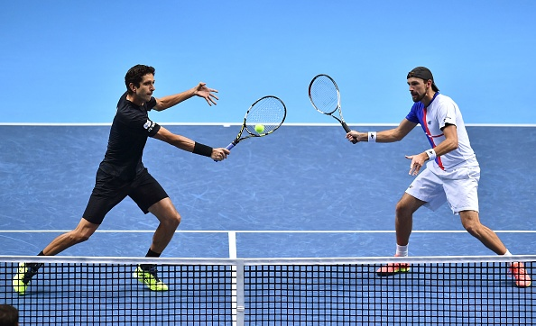 Marcelo Melo strikes a volley with partner Lukasz Kubot besides him (Photo: Glyn Kirk/Getty Images)