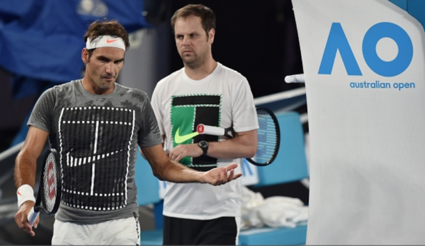 Federer chats with his coach Severin Luthi during a practice session on Rod Laver Arena. Credit: Paul Crock/AFP/Getty Images