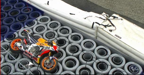 Pedrosa bike mounted the safety barrier following his crash and brsting the air-fence in the process - BT Sport