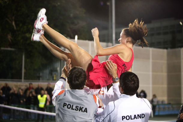 Agnieszka Radwanska is hoisted into the air by her teammates in celebration. Photo: Fed Cup