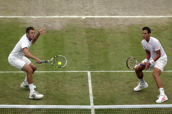 Sock (left) hits a volley as Pospisil watches at Wimbledon in 2014. Photo: Matthew Stockman/Getty Images
