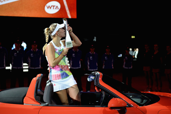Angelique Kerber posing with her trophy in her new Porsche at the Porsche Tennis Grand Prix. | Photo: Dennis Grombkowski