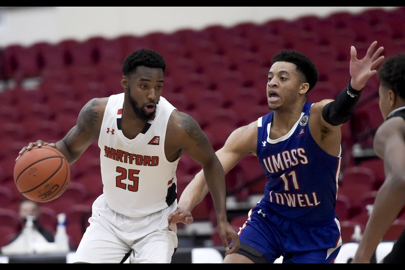 Hartford's Traci Carter (l.) driver past UMass-Lowell's Obadiah Noel (r.) during the America East championship game/Photo: Kassi Jackson/Hartford Courant