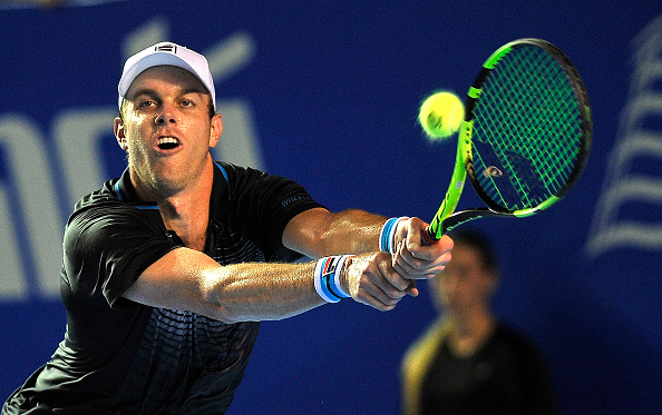 Sam Querrey stretches for a backhand. Photo: Pedro Pardo/AFP/Getty Images