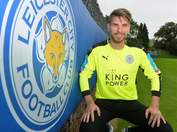 Zieler poses in his new shirt, beside the Leicester City crest. | Image credit: Plumb Images - Leciester City