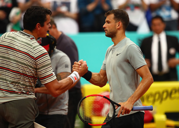 Dimitrov (right) shakes hands with Raonic after his loss in Madrid. Photo: Clive Brunskill/Getty Images