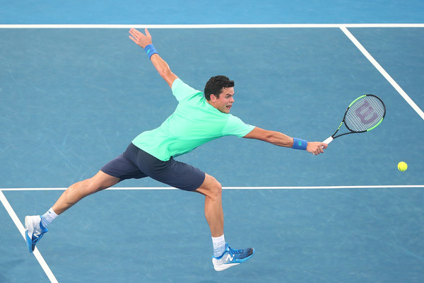 Milos Raonic lunges for a backhand volley. Photo: Chris Hyde/Getty Images