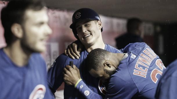 Chicago Cubs' Anthony Rizzo, center, celebrates in the dugout with Jason Heyward after hitting a solo home run off Cincinnati Reds starting pitcher Jon Moscot during the fourth inning  Friday, April 22, 2016, in Cincinnati. (John Minchillo / AP)