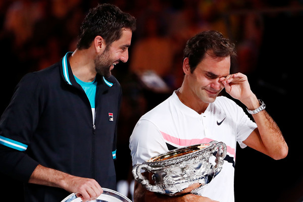 Marin Cilic (L) jokes around with an emotional Roger Federer during the trophy ceremony after battling in the 2018 Australian Open final. | Photo: Roger Federer celebrates after winning a point against Marin Cilic during the final of the 2018 Australian Open. | Photo: Michael Dodge/Getty Images