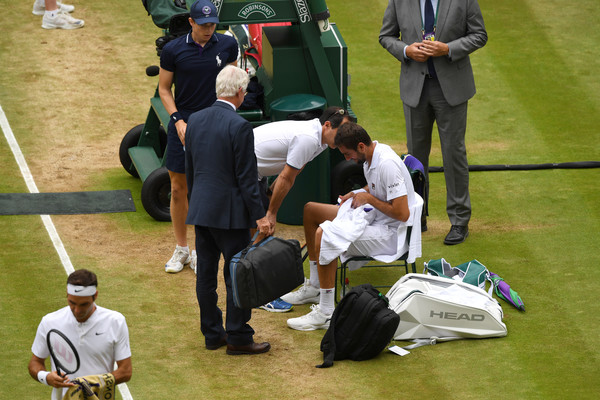Cilic receives assistance at a changeover in the second set (Photo: Clive Brunskill/Getty Images Europe)