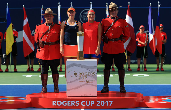 Makarova and Vesnina, together with two members of the Royal Canadian Mounted Police, posing with their title | Photo: Vaughn Ridley/Getty Images North America
