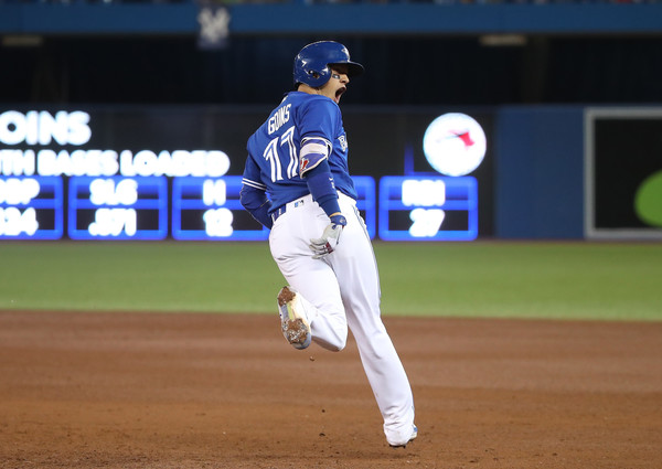 Ryan Goins celebrates while circling the bases after hitting his second-career Grand Slam in the sixth inning to extend Toronto's lead to 8-1.   Photo: Tom Szczerbowski/Getty Images