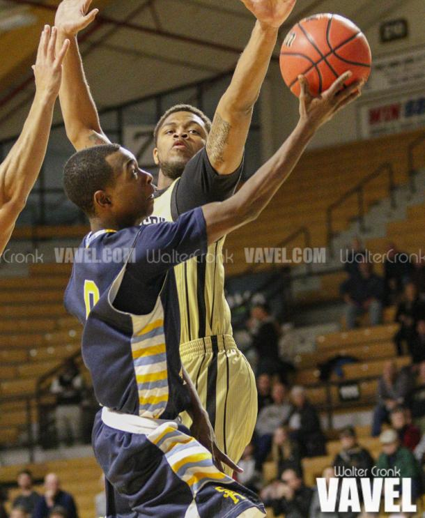 Nick Randle (0) go's in for the lay up against Reggie Jones (23) Photo: Walter Cronk