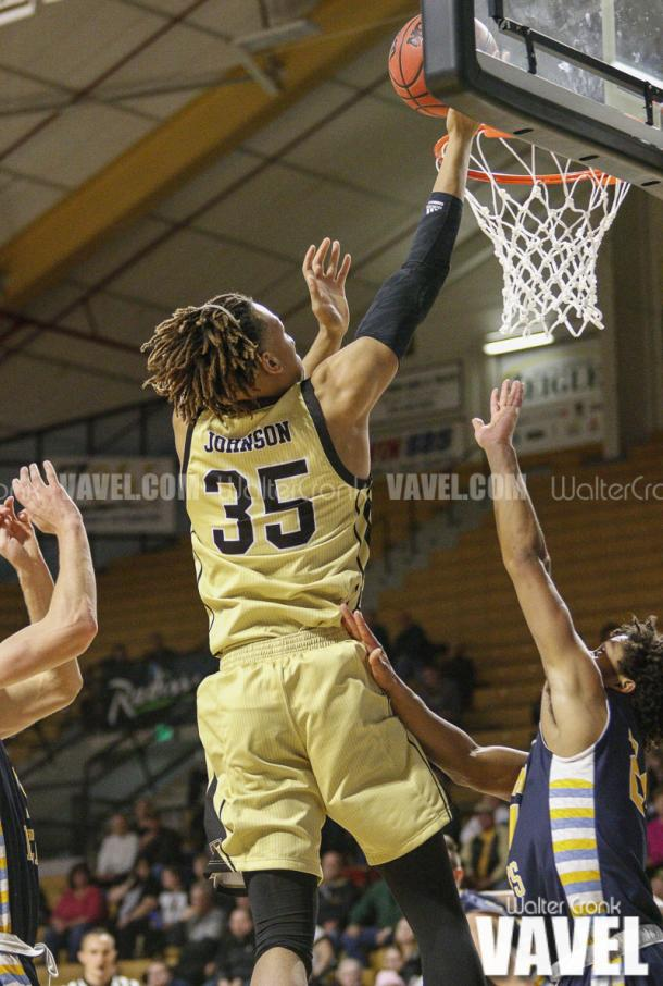 Brandon Johnson (35) gets above Kevin Smith II (24) for the lay up. Photo: Walter Cronk