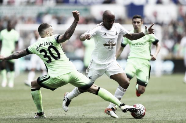 Swansea's Andre Ayew (Center) attempting to get by the Manchester City defense on Sunday at Liberty Stadium. Photo provided by Getty Images.