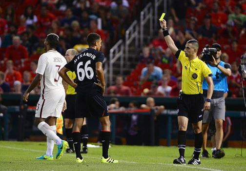 Nima Saghafi hands out a yellow card during a match against Liverpool and Roma in August of 2016 | Source: Jeffy Curry - Getty Images Sport